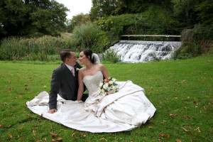 bride & groom sitting by waterfall - wedding photographer in bedfordshire