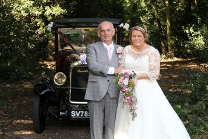 bride & groom standing by vintage car